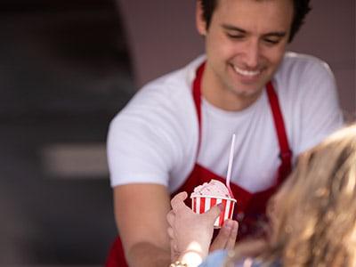 Man handing ice cream to woman in Newport Beach